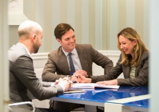 Business people smiling with a client around a table